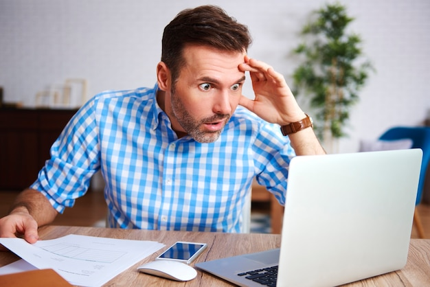 Zszokowany i zmartwiony mężczyzna pracujący w swoim biurze