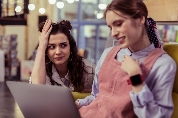 Zszokowany informacjami. zdezorientowana ciemnowłosa dziewczyna niewiarygodnie patrzy na swojego uśmiechniętego przyjaciela, gdy pisze na laptopie
