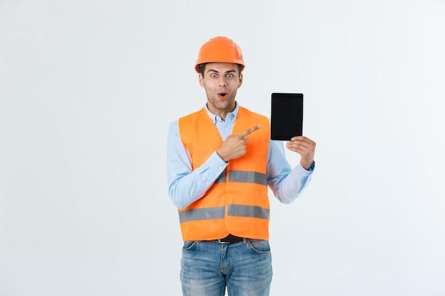 Zszokowany inżynier pokazujący ekran tabletu, patrzy z otwartymi ustami, jak wspomina ważne spotkanie. mężczyzna w stresującej sytuacji. koncepcja niespodzianka i szok.