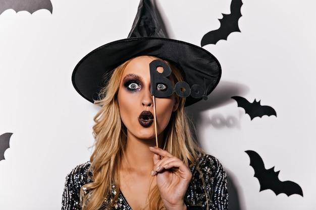 Zszokowany kaukaski kobieta z szarymi oczami pozuje w halloween. kryty zdjęcie wampira debonair na białym tle na białej ścianie.