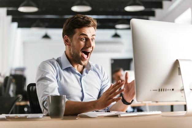 Zszokowany krzyczący biznesmen przy użyciu komputera siedząc przy stole w biurze