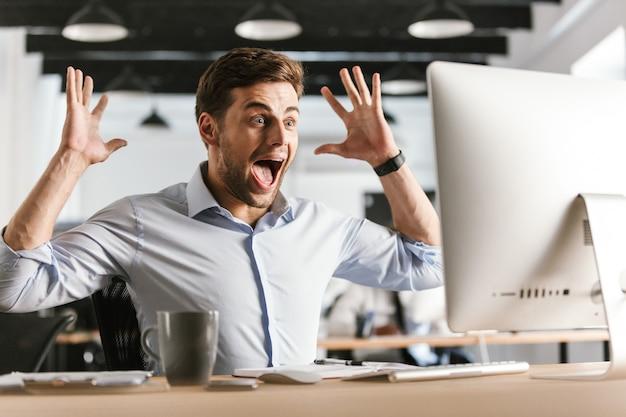 Zszokowany krzyczący biznesmen za pomocą komputera i raduje się, siedząc przy stole w biurze