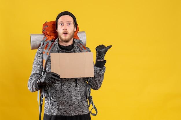 Zszokowany mężczyzna autostopowicz w skórzanych rękawiczkach i plecaku trzymającym pusty karton wskazujący na coś