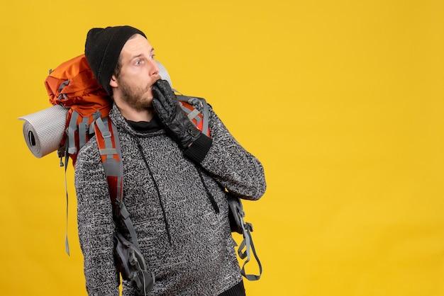 Zszokowany mężczyzna autostopowicz w skórzanych rękawiczkach i plecaku wpatrujący się w coś