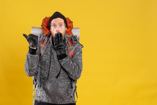 Zszokowany mężczyzna autostopowicz w skórzanych rękawiczkach i plecaku