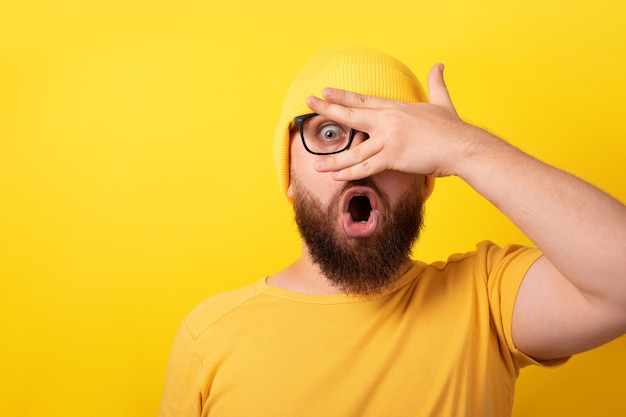 Zszokowany mężczyzna patrzący przez palce na żółtym tle