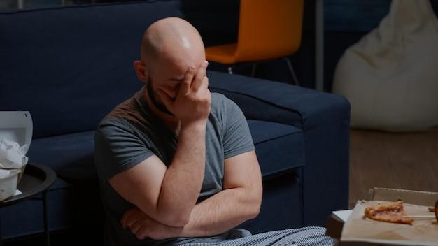 Zszokowany mężczyzna siedzący na podłodze w domu, czytający złe wieści, trzymający dokumenty