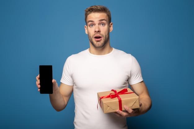 Zszokowany mężczyzna trzyma smartphone i pudełko na niebieskim tle