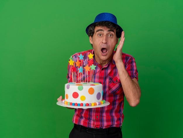Zszokowany mężczyzna w średnim wieku kaukaski imprezowicz w kapeluszu imprezowym, trzymając tort urodzinowy, patrząc na kamerę, trzymając rękę blisko głowy, patrząc na kamerę odizolowaną na zielonym tle z przestrzenią do kopiowania