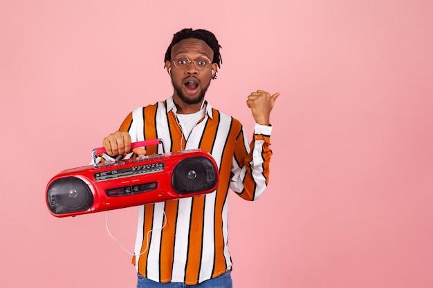 Zszokowany mężczyzna z magnetofonem słuchającym muzyki i wskazującym na wolną przestrzeń na reklamę
