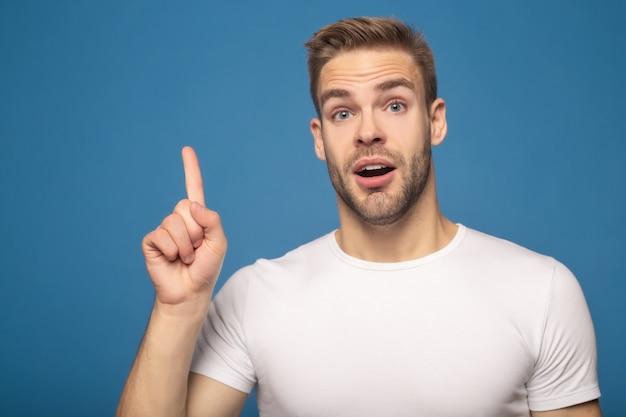 Zszokowany mężczyzna z otwartymi ustami pokazano pomysł gest na niebieskim tle