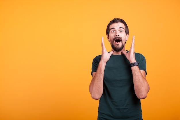 Zszokowany mężczyzna z rękami na twarzy patrząc w kamerę. copyspace dostępne dla twojej reklamy lub promocji