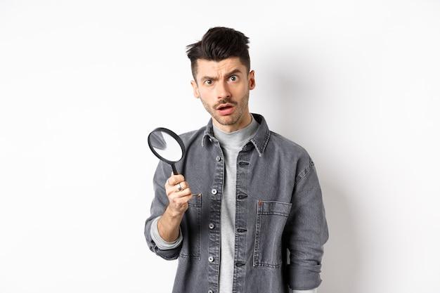 Zszokowany mężczyzna znalazł coś z lupą, spojrzał na aparat, stojąc na białym tle.