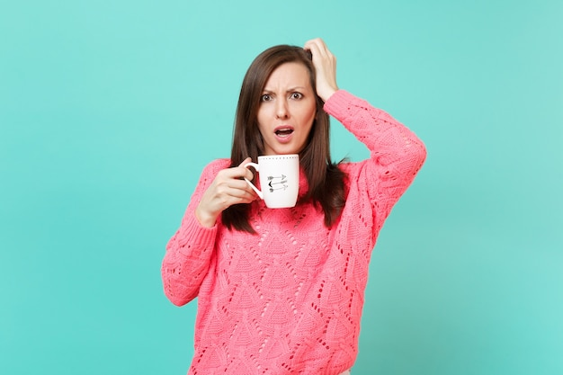 Zszokowany młoda kobieta w różowy sweter z dzianiny, kładąc rękę na głowie trzymając filiżankę kawy lub herbaty na białym tle na tle niebieskiej ściany turkus, portret. koncepcja życia ludzi. makieta miejsca na kopię.