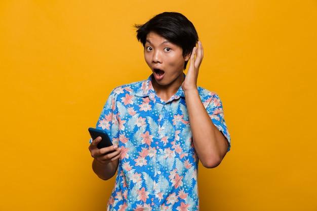 Zszokowany młody azjatycki mężczyzna stojący na białym tle nad żółtą przestrzenią za pomocą telefonu komórkowego.