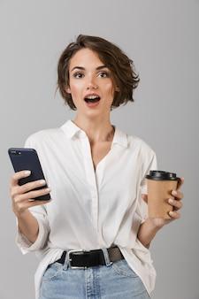 Zszokowany młody biznes kobieta pozowanie na białym tle nad szarą ścianą na czacie przez telefon komórkowy picia kawy