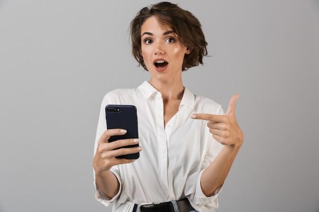 Zszokowany młody biznes kobieta pozowanie na białym tle nad szarą ścianą za pomocą telefonu komórkowego i na czacie