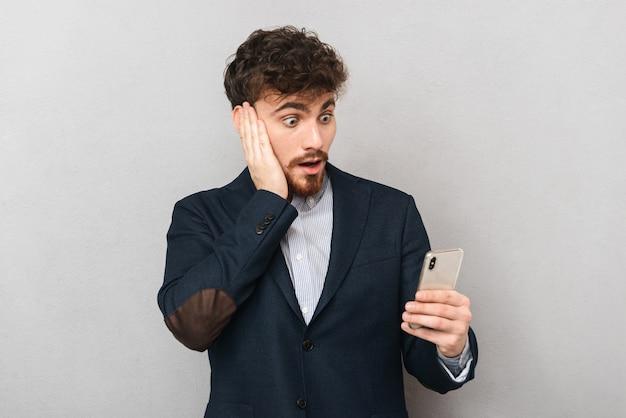 Zszokowany młody biznesmen ubrany w garnitur stojący na białym tle nad szarym, trzymając telefon komórkowy