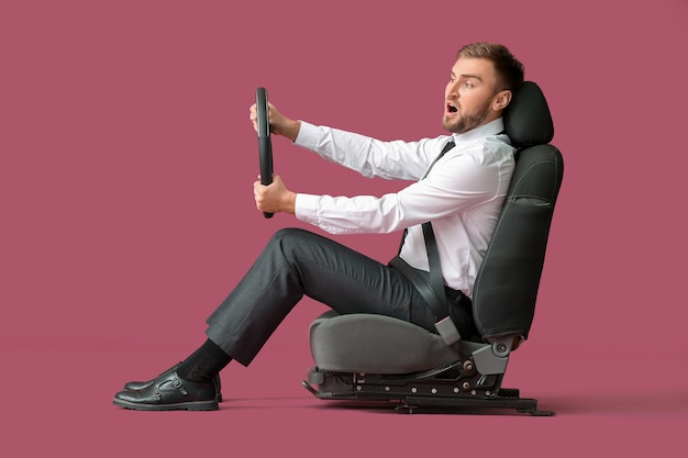 Zszokowany młody biznesmen z kierownicą siedzi na fotelu samochodowym przed kolorowym tłem