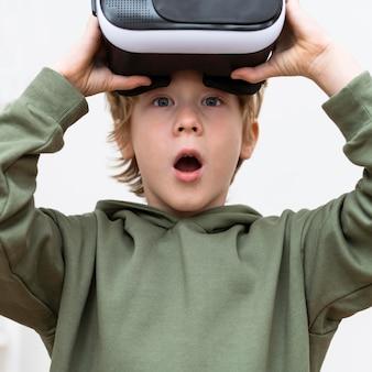 Zszokowany młody chłopak za pomocą zestawu słuchawkowego wirtualnej rzeczywistości