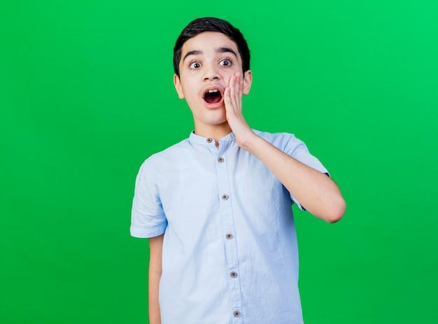 Zszokowany młody chłopiec kaukaski patrząc na bok, trzymając rękę na twarzy na białym tle na zielonej ścianie z miejsca na kopię