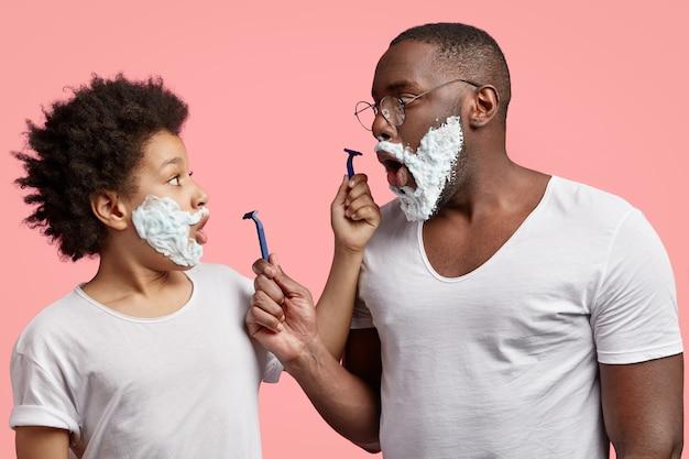 Zszokowany młody człowiek i jego syn z pianką do golenia na twarzach, trzymają szczęki opuszczone, trzymają brzytwy,