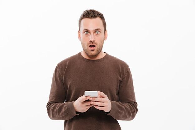 Zszokowany młody człowiek na czacie przez telefon komórkowy