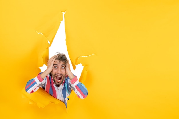Zszokowany młody człowiek pozuje w podartym żółtym tle dziury w papierze