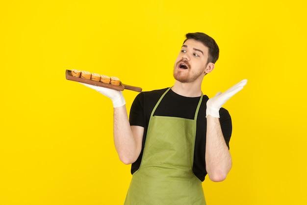 Zszokowany młody człowiek trzyma kupie kromki ciasta na drewnianej tacy.