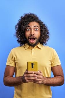 Zszokowany, młody człowiek, trzymając smartfon, czytał, otrzymał powiadomienie typu krzyk omg, jest zaskoczony wiadomościami lub wiadomością, odizolowany