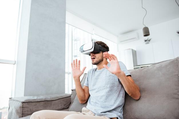 Zszokowany młody człowiek ubrany w urządzenie wirtualnej rzeczywistości siedząc na kanapie
