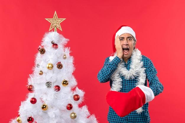 Zszokowany młody człowiek w kapeluszu świętego mikołaja w niebieskiej koszuli w paski i noszący swoją świąteczną skarpetę