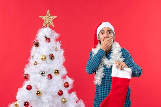 Zszokowany młody człowiek w kapeluszu świętego mikołaja w niebieskiej koszuli w paski i trzymający świąteczną skarpetę zamknął usta
