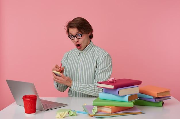 Zszokowany młody człowiek w okularach siedzi przy stole i pracuje z laptopem, zapisuje rozwiązanie równania na naklejkach izolowanych na różowym tle.