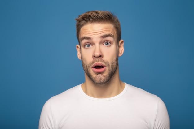 Zszokowany młody człowiek z otwartymi ustami na niebieskim tle