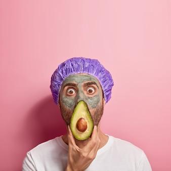 Zszokowany młody człowiek zakrywa nos i usta kawałkiem świeżego awokado, ma wyskakujące oczy, nosi glinianą maskę dla dobrego efektu, wodoodporne nakrycie głowy, wykonuje zabiegi kosmetyczne w centrum spa