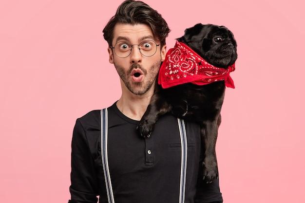 Zszokowany młody freelancer o specyficznym wyglądzie spędza wolny czas w towarzystwie psa, ma zdziwiony wyraz twarzy, gapi się, pozuje na różowej ścianie. koncepcja ludzi i zwierząt