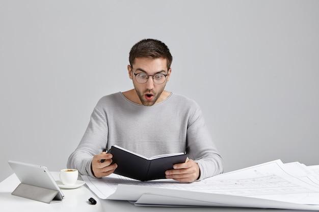 Zszokowany młody inżynier mężczyzna w stylowych okrągłych okularach trzyma czarny notes, szeroko otwierając usta ze zdziwienia