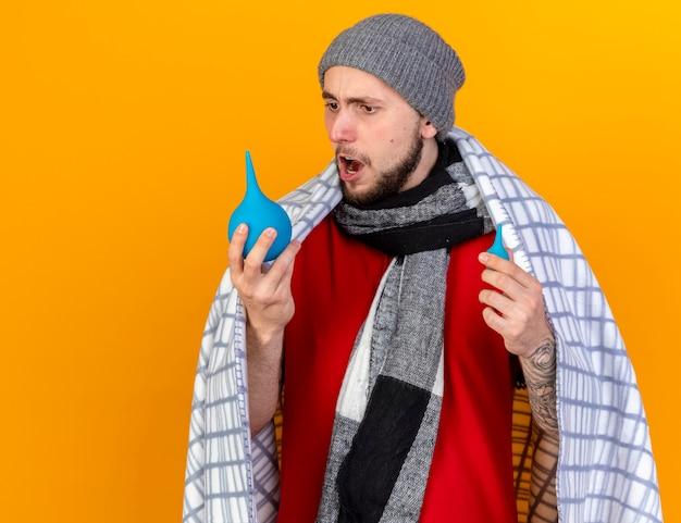 Zszokowany młody kaukaski chory ubrany w czapkę zimową i szalik zawinięty w kratę trzyma i wygląda