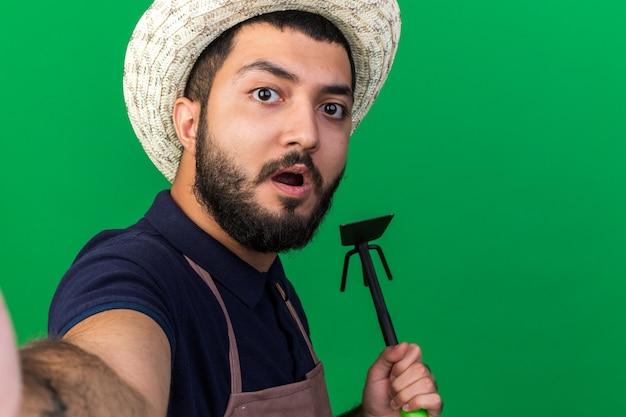 Zszokowany młody kaukaski mężczyzna ogrodnik w kapeluszu ogrodniczym trzyma grabie motykę biorąc selfie na zielonej ścianie z kopią przestrzeni