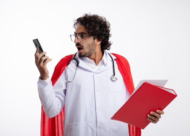 Zszokowany młody kaukaski mężczyzna superbohatera w okularach optycznych w mundurze lekarza z czerwonym płaszczem i stetoskopem na szyi trzyma folder plików i patrzy na telefon na białej ścianie