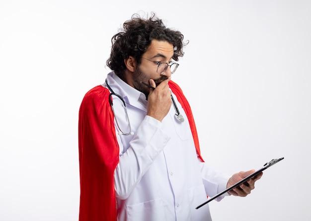 Zszokowany młody kaukaski mężczyzna w okularach optycznych w mundurze lekarza z czerwonym płaszczem i stetoskopem na szyi patrzy na schowek kładąc rękę na ustach trzymając ołówek z miejscem na kopię