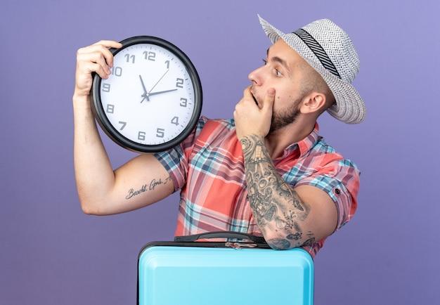 Zszokowany młody podróżnik kaukaski mężczyzna ze słomkowym kapeluszem na plaży trzymający i patrzący na zegar stojący za walizką na białym tle na fioletowym tle z kopią przestrzeni