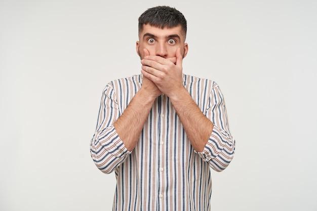 Zszokowany młody przystojny ciemnowłosy brodaty mężczyzna zaokrąglający oczy, patrząc i zakrywający usta uniesionymi rękami, odizolowany na białej ścianie