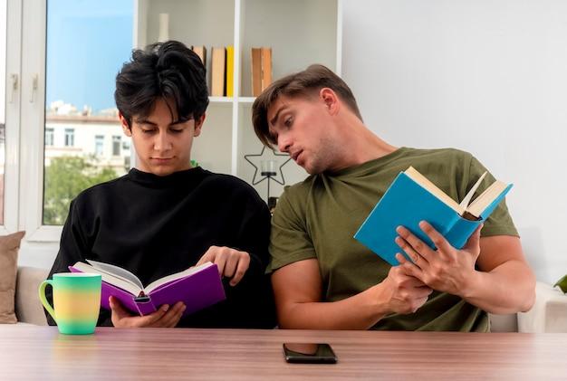 Zszokowany młody przystojny mężczyzna blondynka trzyma książkę siedząc przy stole i patrząc na książkę zadowolony młody przystojny facet brunetka wewnątrz salonu
