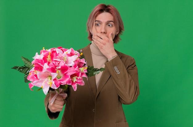 Zszokowany młody przystojny mężczyzna kładący rękę na ustach, trzymający i patrzący na bukiet kwiatów