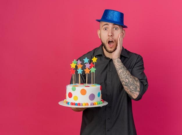 Zszokowany młody przystojny słowiański imprezowicz w kapeluszu imprezowym, trzymając tort urodzinowy z gwiazdami, trzymając rękę na twarzy, patrząc na kamerę na białym tle na szkarłatnym tle z miejsca na kopię