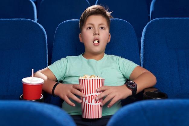 Zszokowany nastolatek z otwartymi ustami ogląda film w kinie