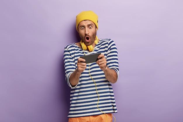 Zszokowany nieogolony facet trzyma telefon komórkowy poziomo, wstrzymuje oddech, gra w gry online, jest uzależniony, nosi żółtą czapkę i sweter w paski
