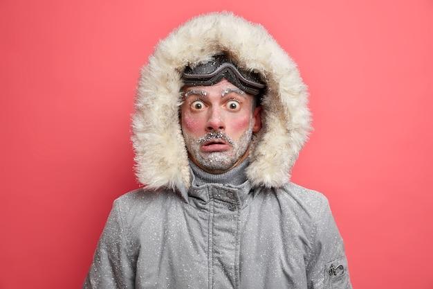 Zszokowany nieogolony mężczyzna nosi ciepłą kurtkę z kapturem, idealną na mroźne zimowe dni, ma twarz pokrytą śniegiem, nie przystosowany do silnych mrozów, ma aktywny wypoczynek.